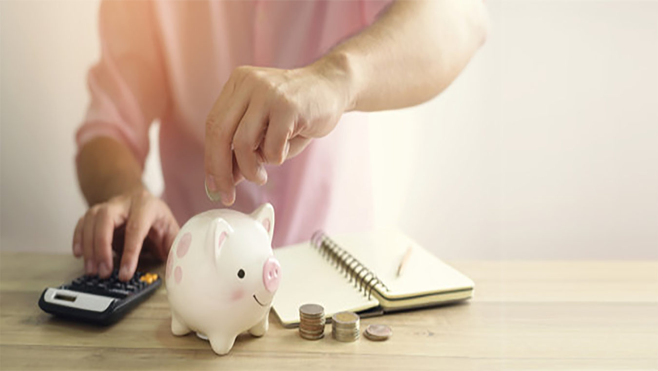 Money being put in piggy bank whilst typing on calculator